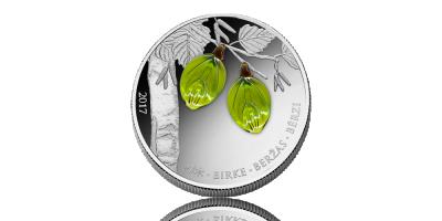 Sølvmønt med to grønne birkeblader i krystal